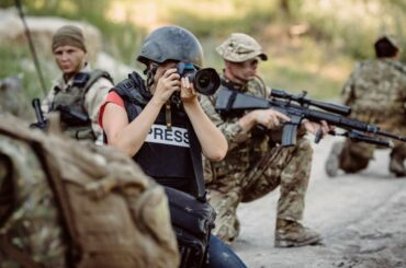 Press journalist photographing war scene